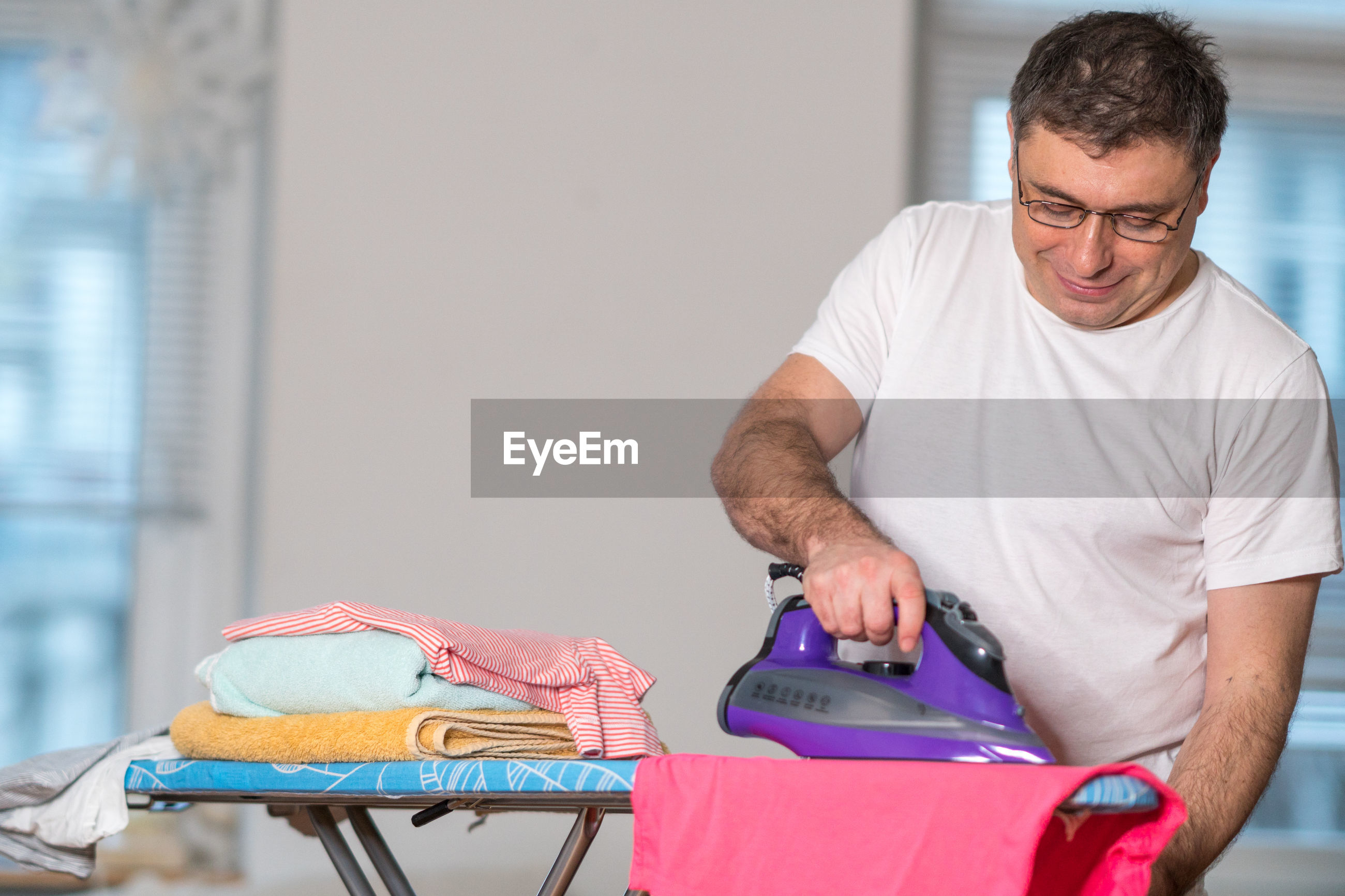 Man ironing cloth at home