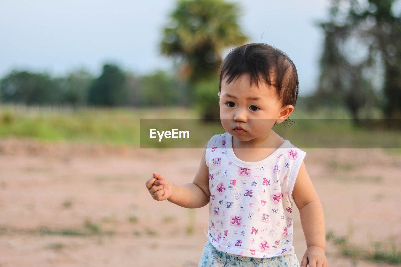 childhood, child, innocence, real people, one person, cute, focus on foreground, front view, girls, casual clothing, field, lifestyles, leisure activity, standing, day, waist up, outdoors