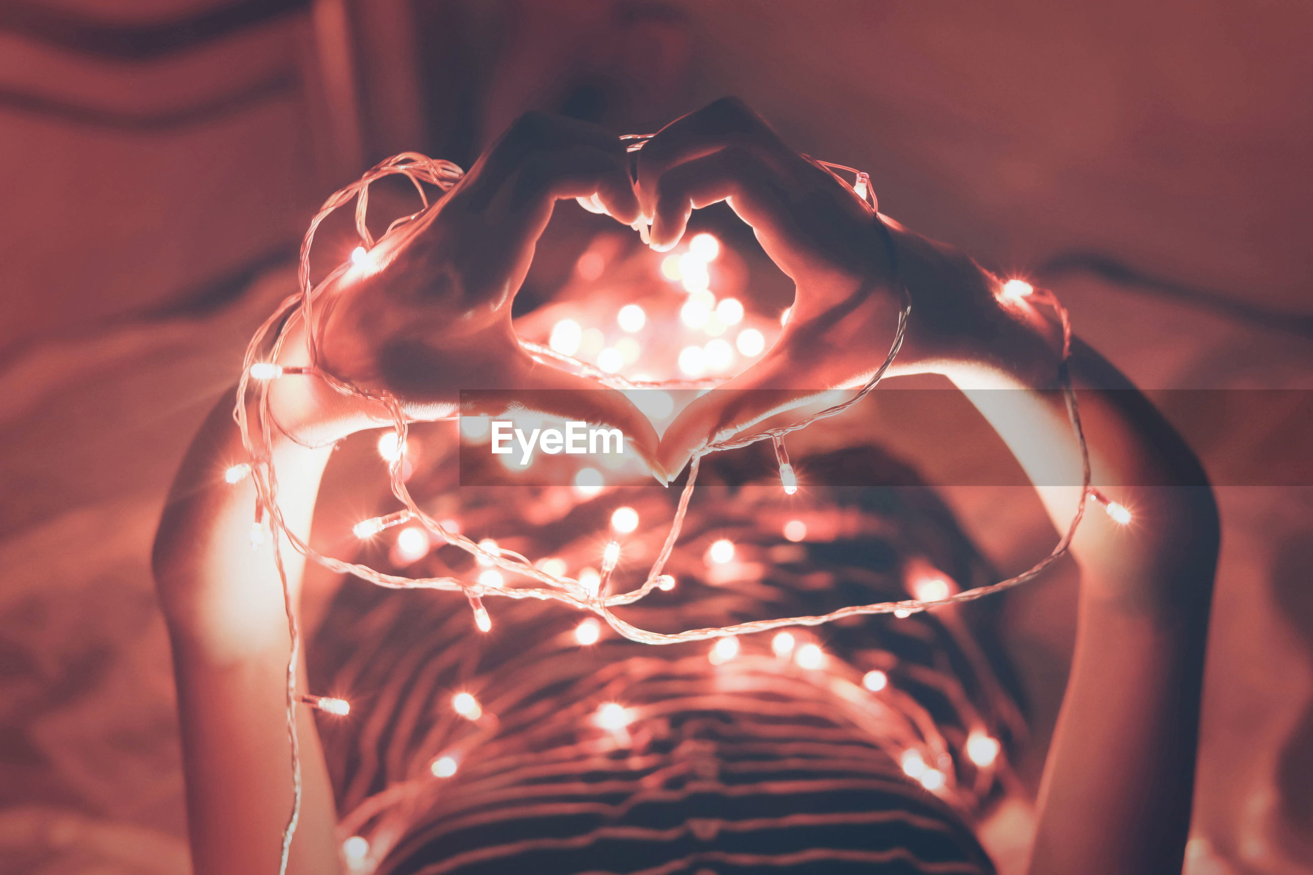 High angle view of hands forming heart shape next to illuminated lights