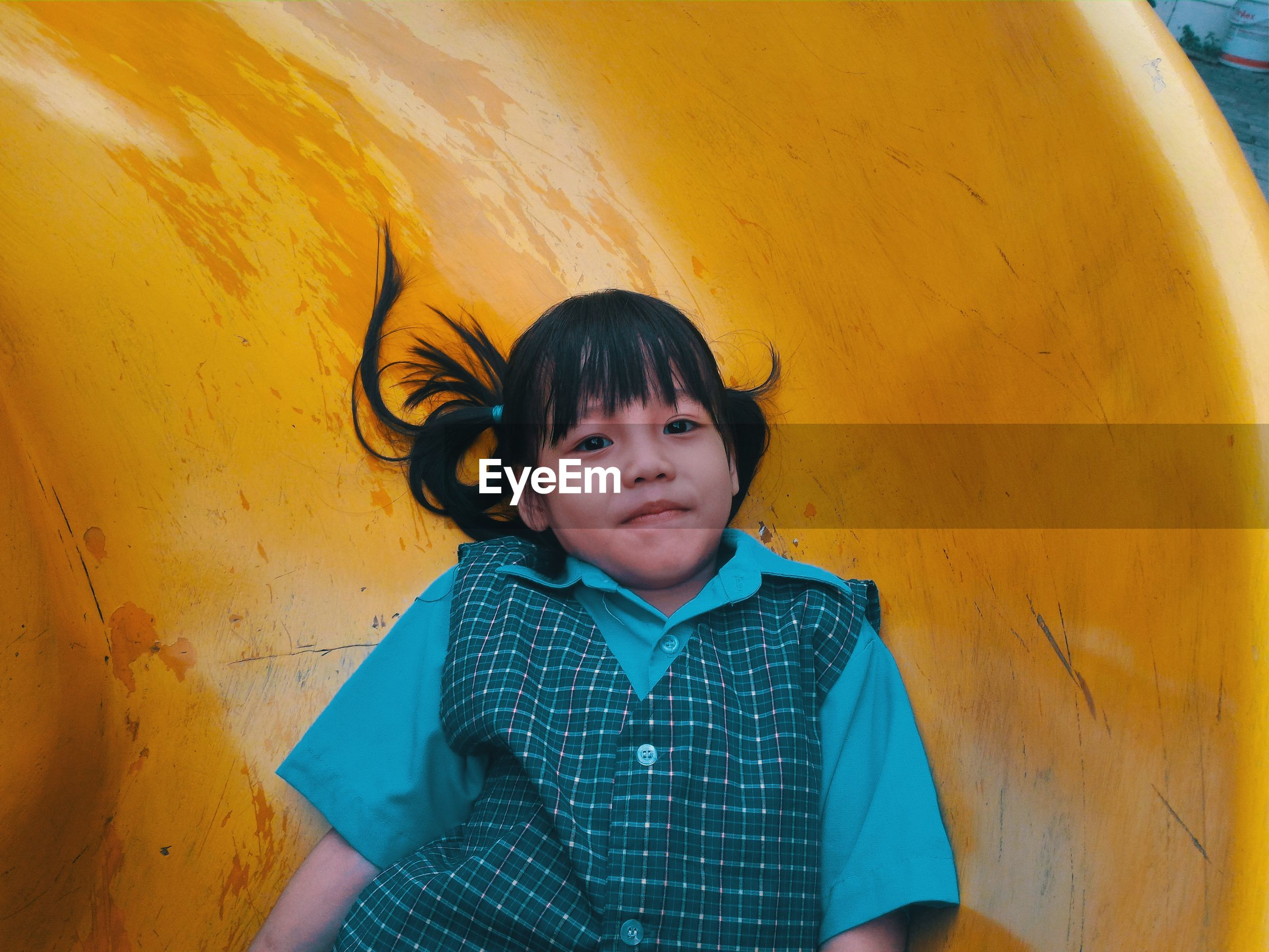 Portrait of cute girl on yellow slide