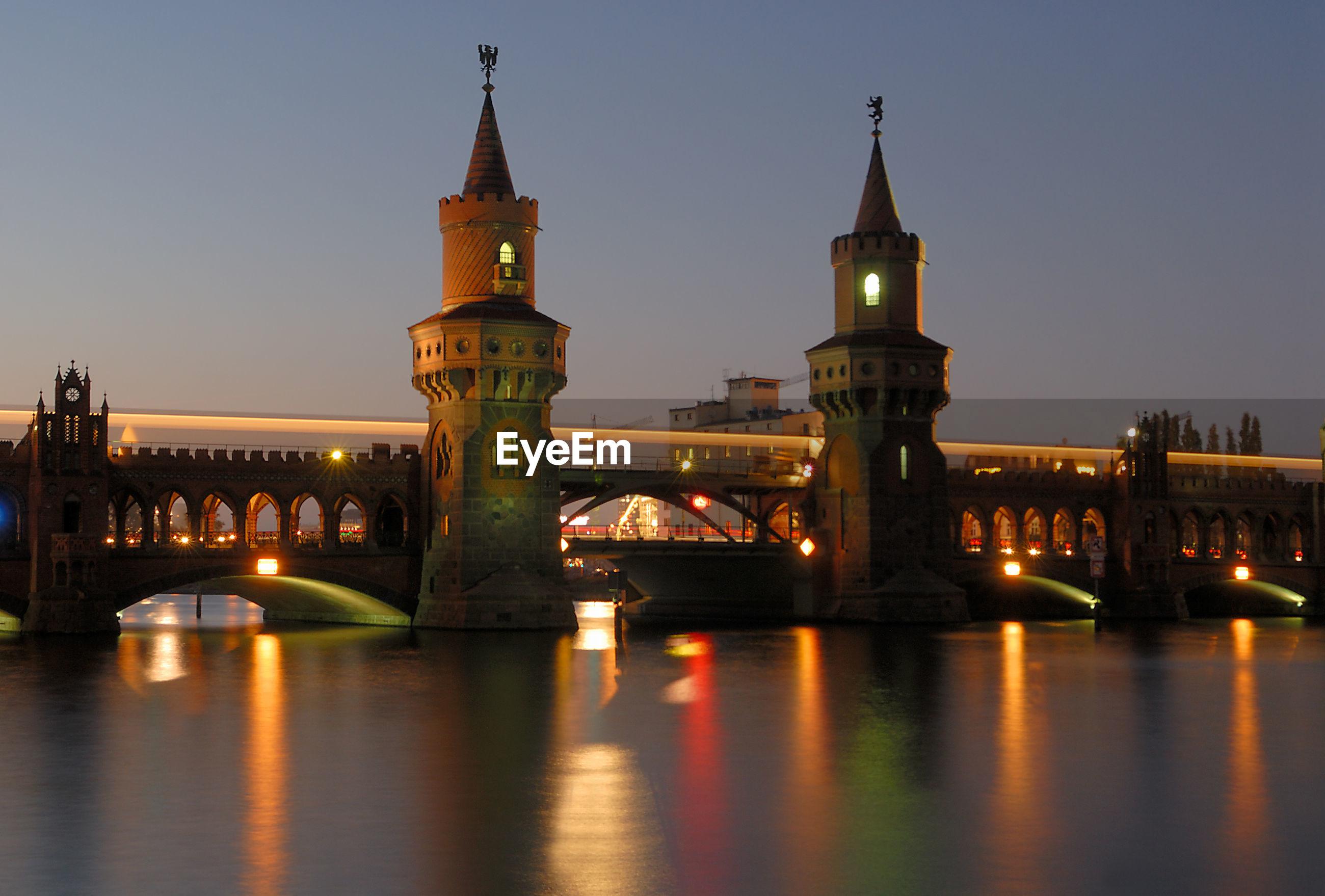 Illuminated oberbaum bridge over river at night