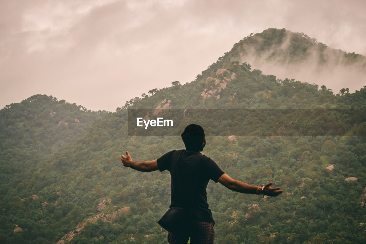 Rear view of man with arms outstretched looking at mountains against sky