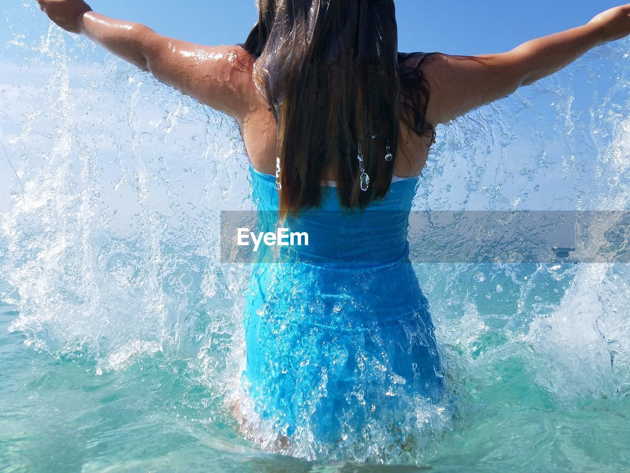 Midsection of girl splashing water in sea