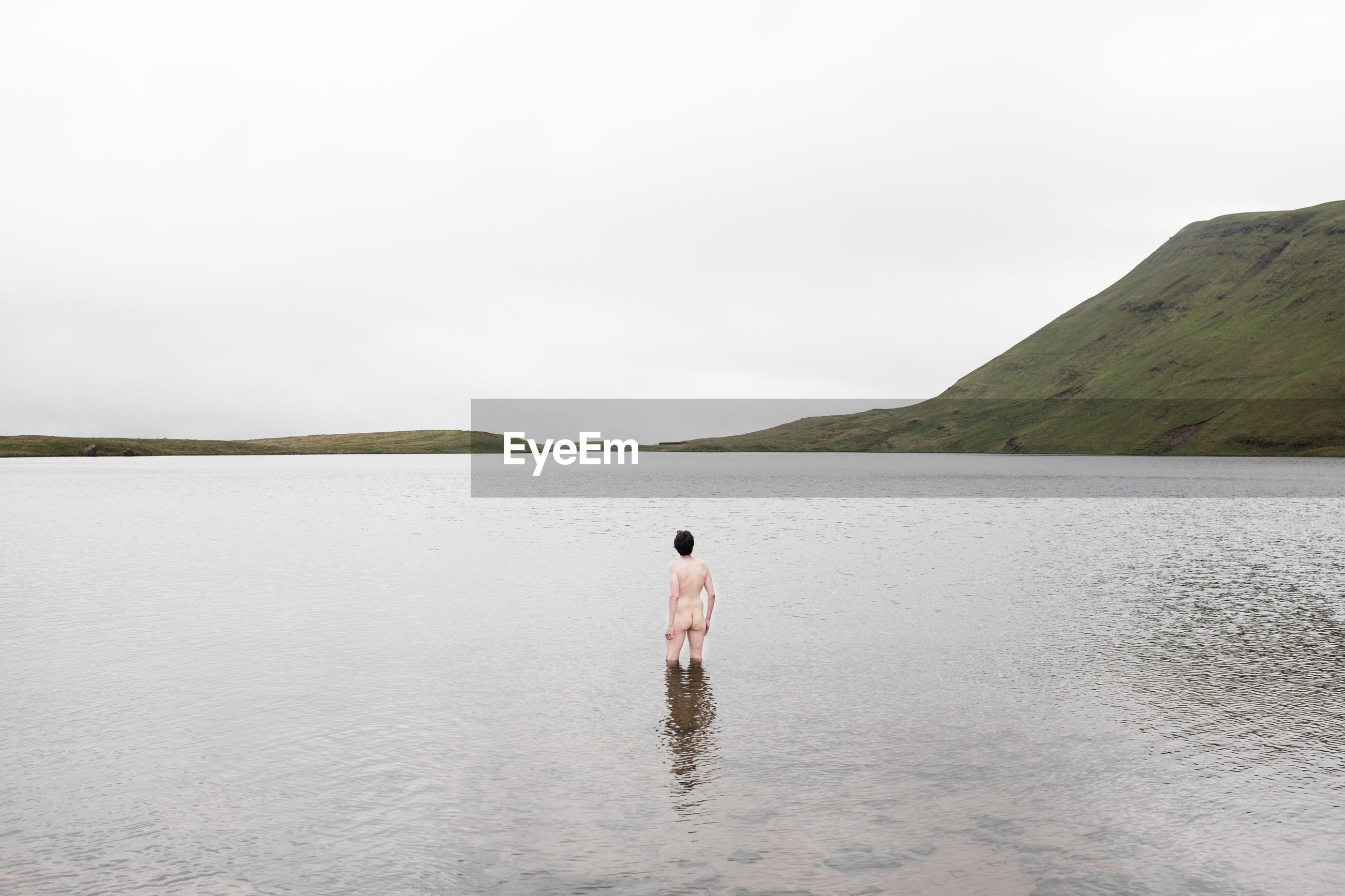 Naked man standing in lake against sky