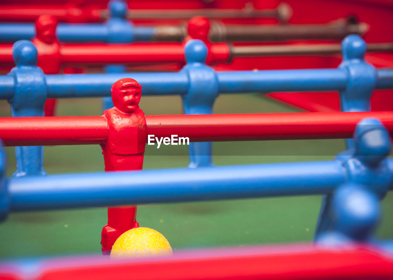 red, sport, close-up, no people, leisure games, blue, soccer, team sport, metal, competition, relaxation, in a row, human representation, leisure activity, full frame, selective focus, figurine, multi colored, day, indoors