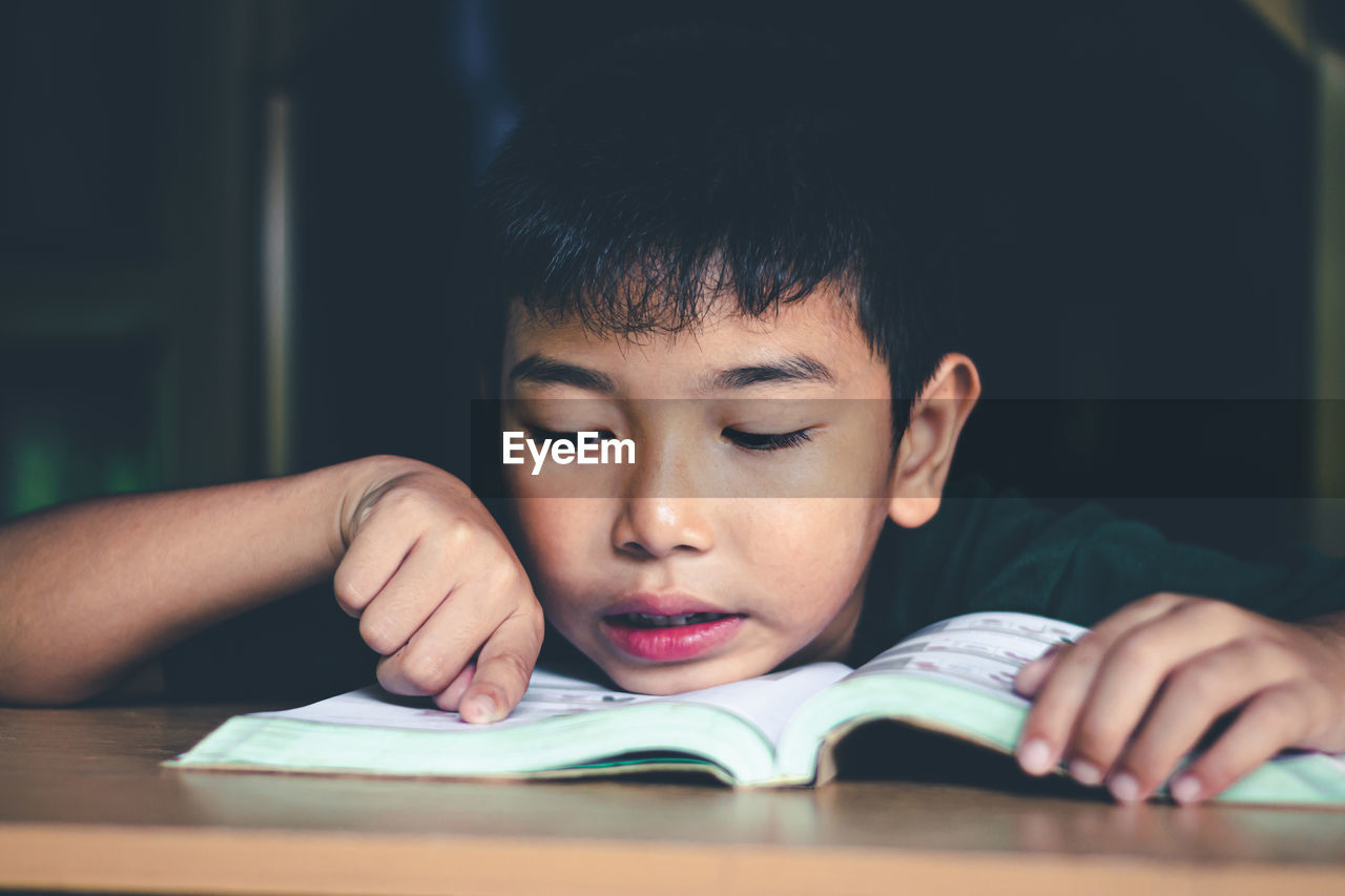 The boy was reading a book in a quiet room, concept read a book.
