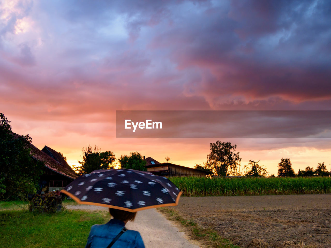 Rear view of mature woman with umbrella standing on road against cloudy sky during sunset