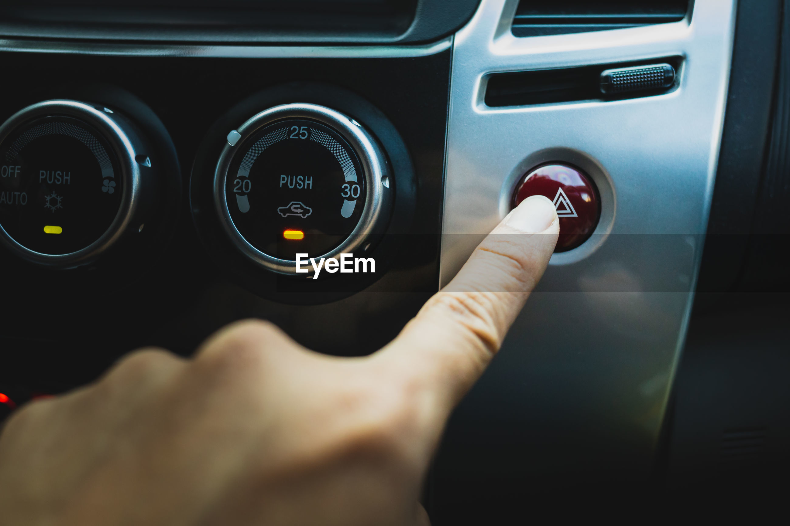 Close up men hand are pressing the emergency light button in the car