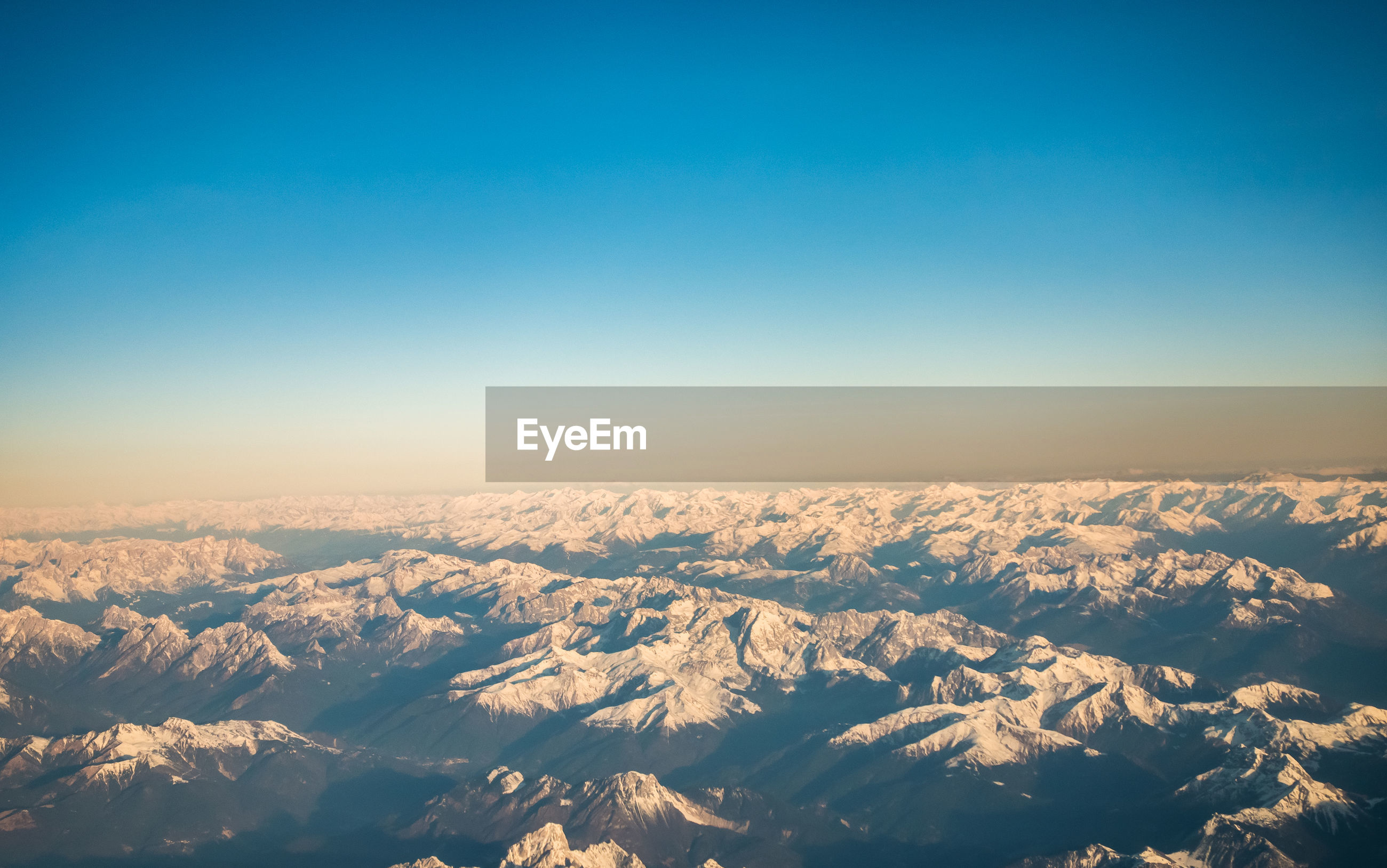 AERIAL VIEW OF SNOWCAPPED MOUNTAIN AGAINST CLEAR SKY