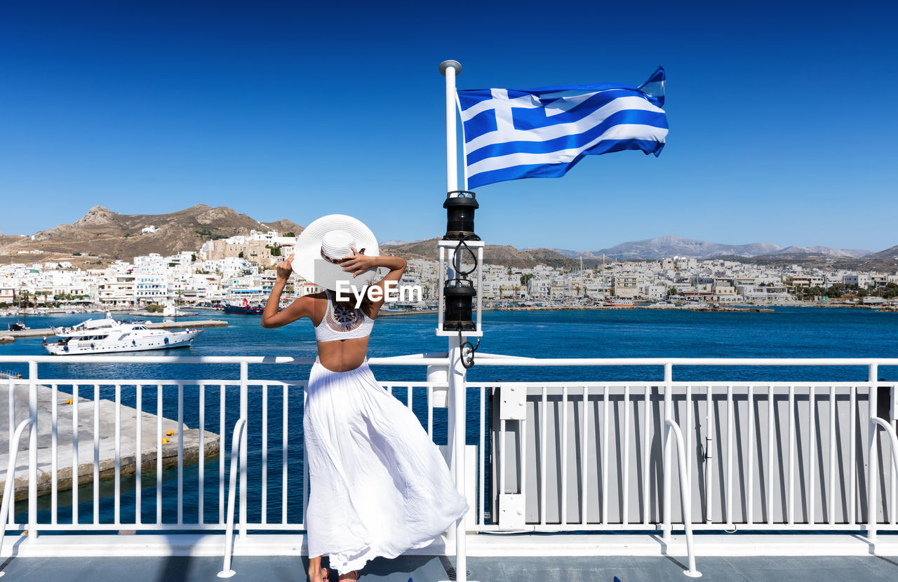Rear View Of Woman Wearing White Dress While Standing By Railing Against Clear Blue Sky