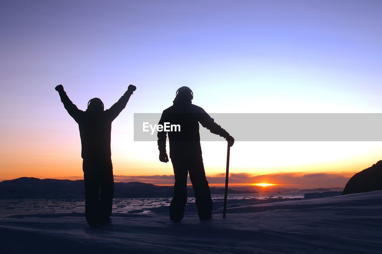 Silhouette Friends Standing On Snowcapped Mountains At Sunset