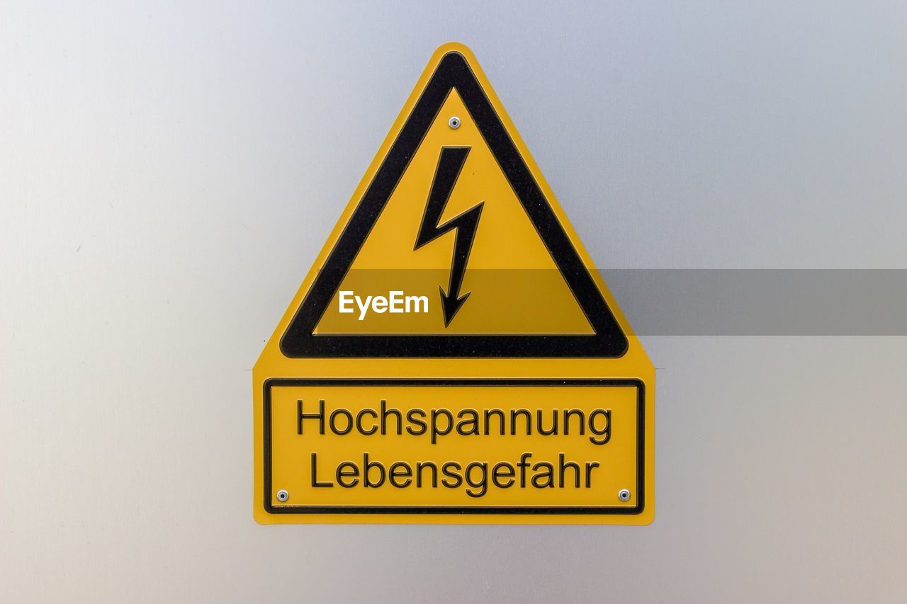 yellow, communication, sign, warning sign, shape, triangle shape, text, high voltage sign, safety, information, no people, information sign, design, geometric shape, warning symbol, electricity, security, protection, close-up, western script