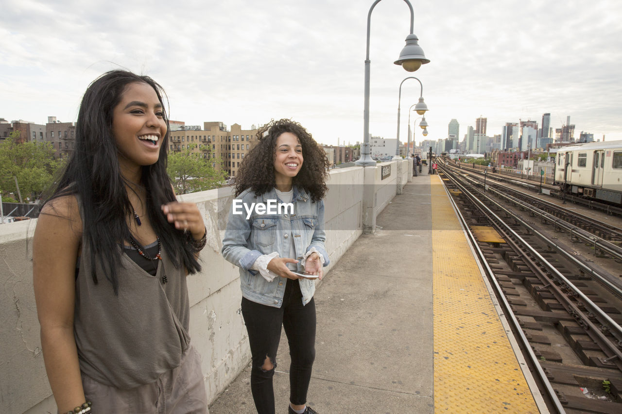 Young women waiting at a train station in queens