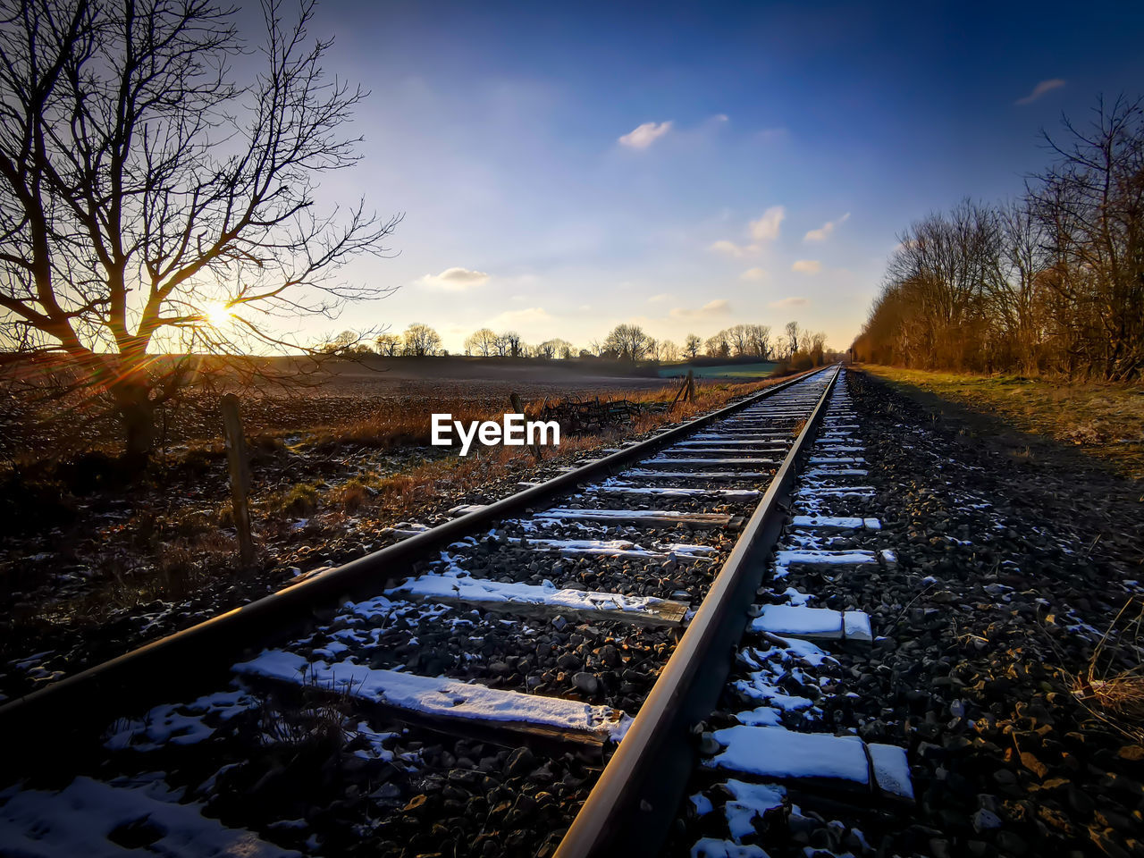 SURFACE LEVEL VIEW OF RAILROAD TRACKS AGAINST SKY