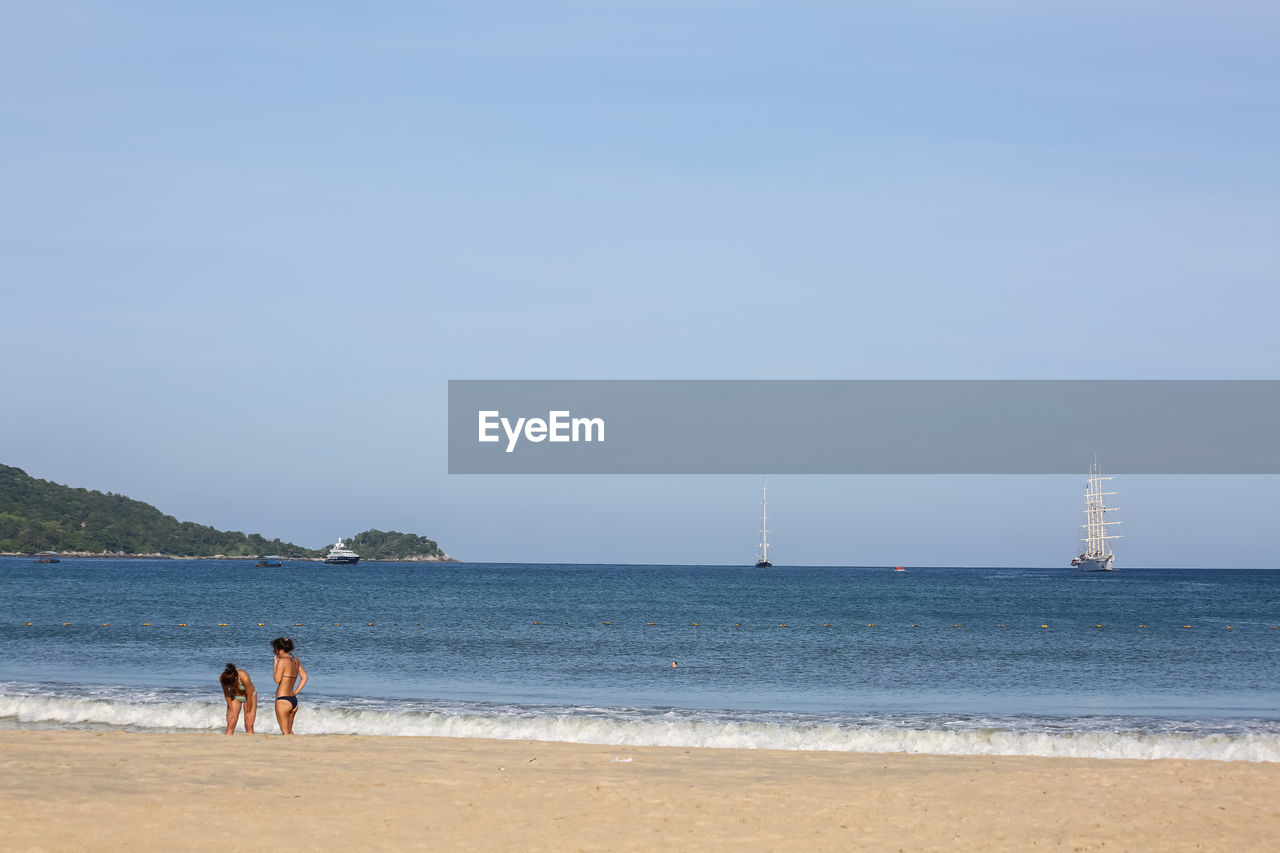 Distant View Of Female Friends Standing At Beach Against Sky