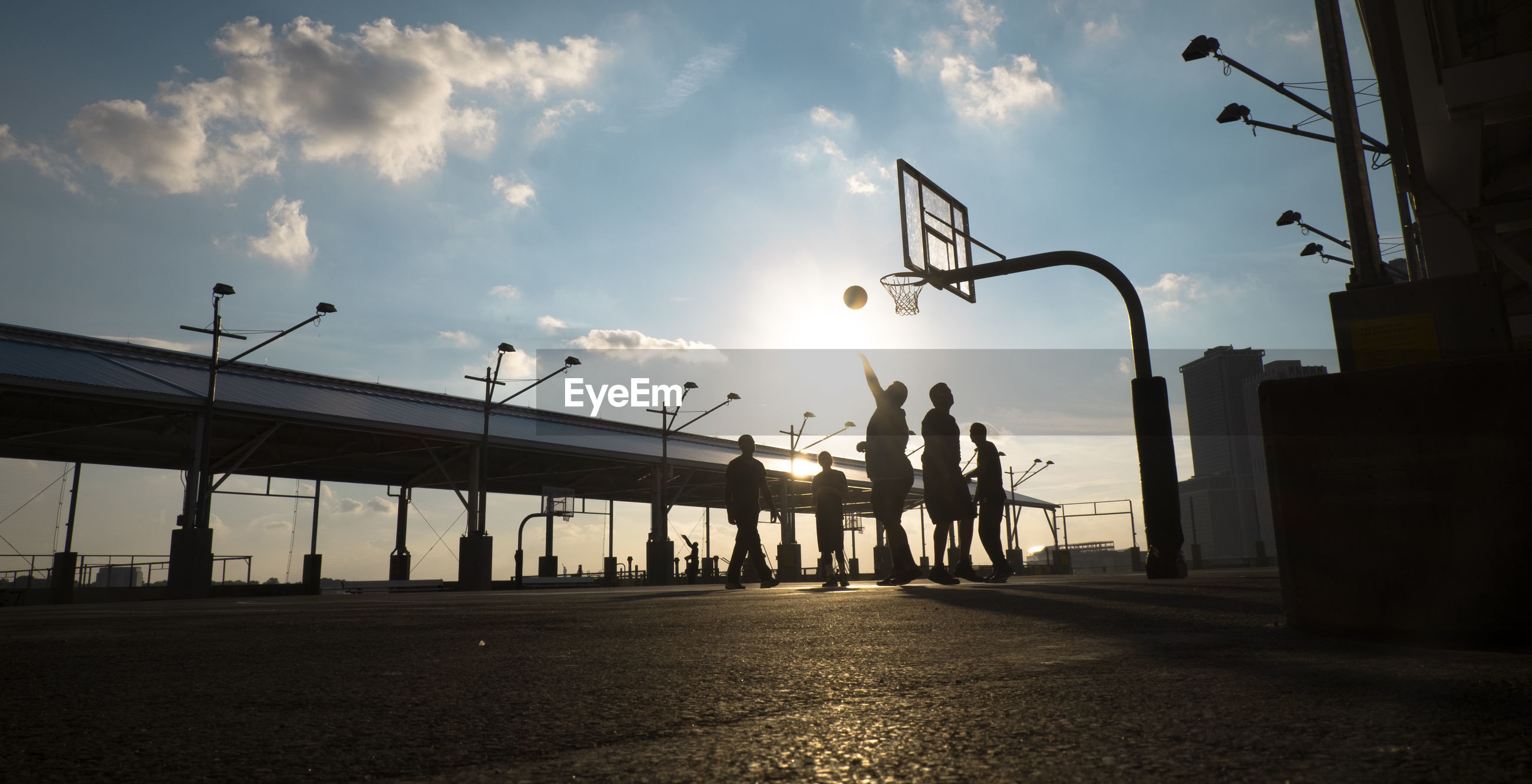 Silhouette men playing basketball by bridge against sky