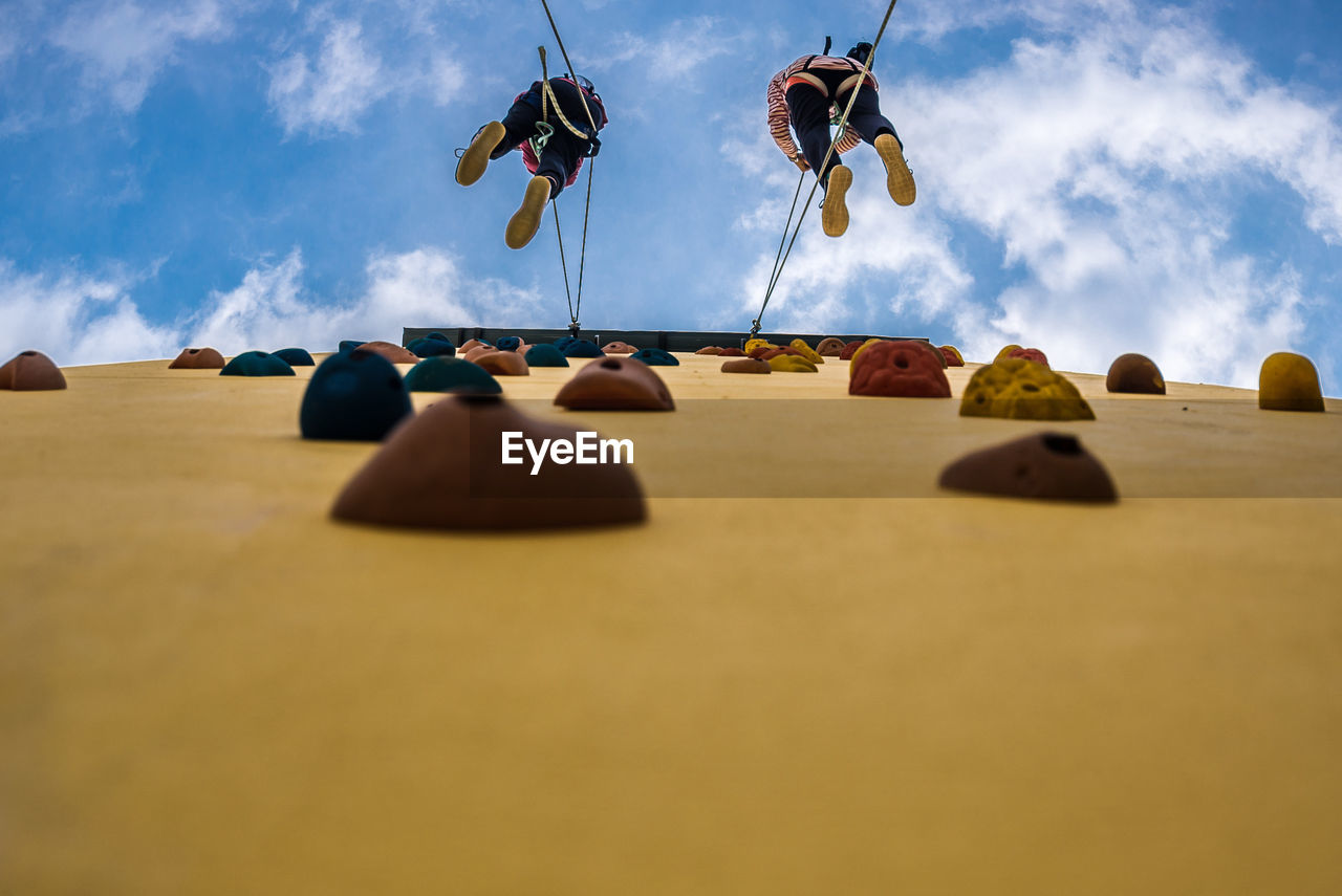 Low angle view of people climbing on wall against sky