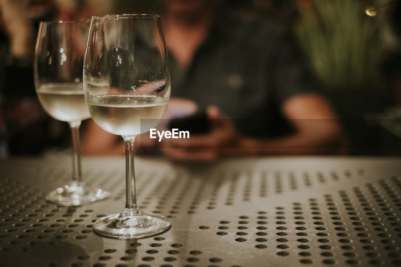refreshment, wineglass, glass, alcohol, drink, wine, food and drink, table, indoors, transparent, focus on foreground, glass - material, red wine, close-up, business, freshness, real people, one person, restaurant, household equipment