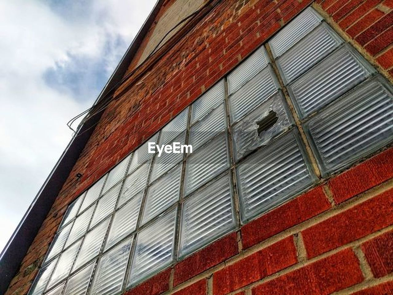 low angle view, built structure, architecture, building exterior, sky, building, day, no people, cloud - sky, window, nature, outdoors, red, pattern, brick wall, wall, brick, wall - building feature, city, glass - material