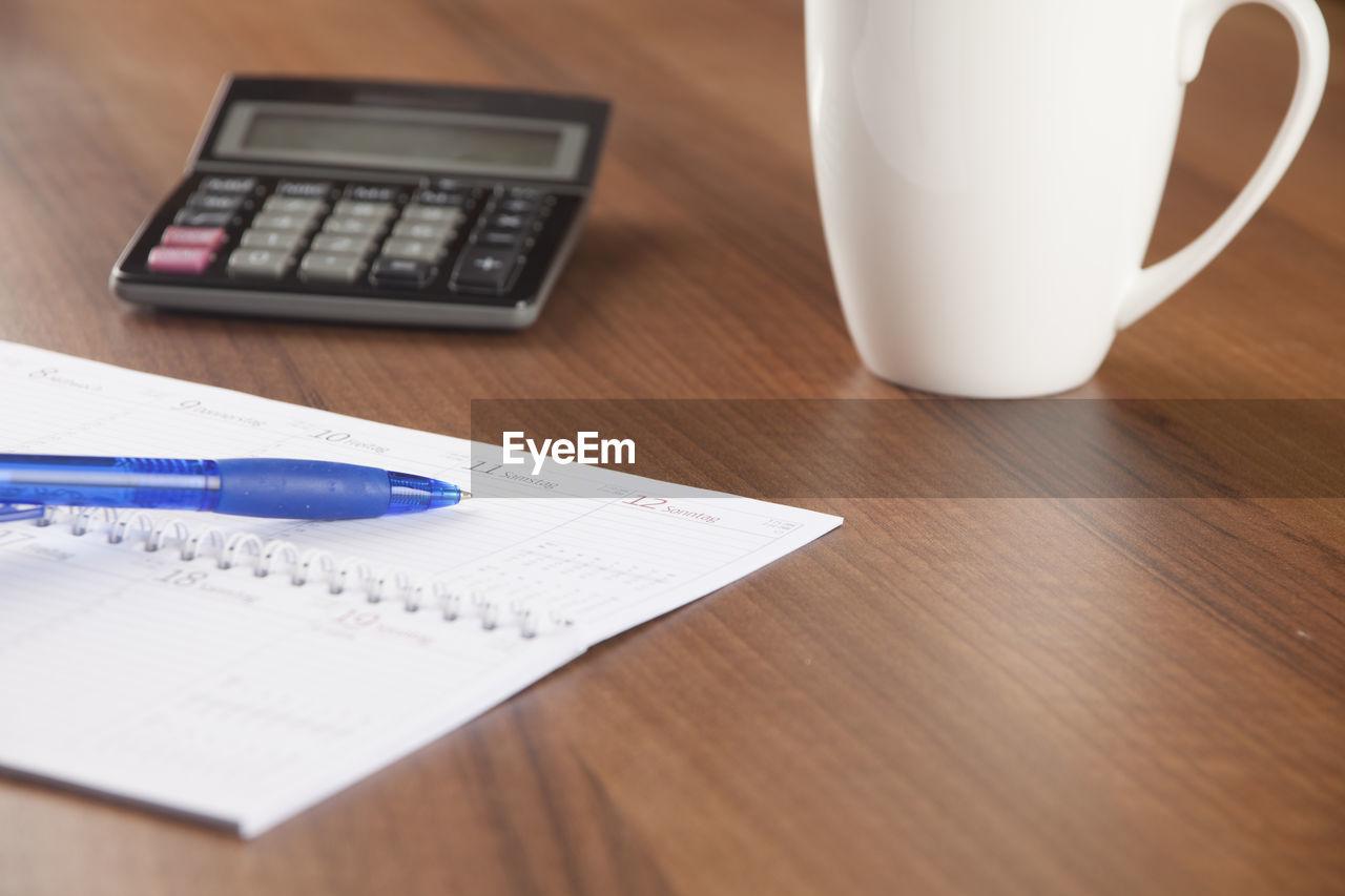 calculator, indoors, table, still life, mathematics, desk, finance, coffee cup, paper, high angle view, coffee - drink, no people, close-up, budget, technology, day