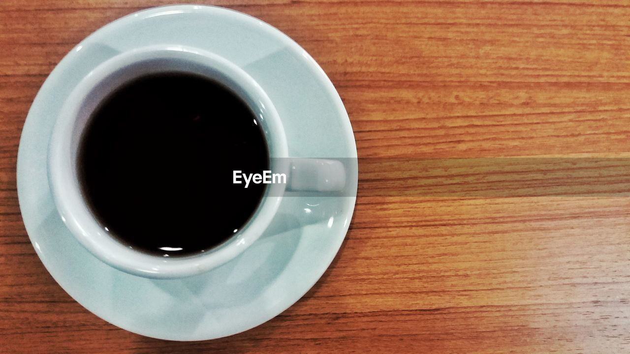 drink, refreshment, cup, mug, coffee, coffee - drink, food and drink, table, coffee cup, crockery, black coffee, directly above, wood - material, indoors, freshness, saucer, black tea, close-up, still life, non-alcoholic beverage, no people, tea cup, caffeine, wood grain