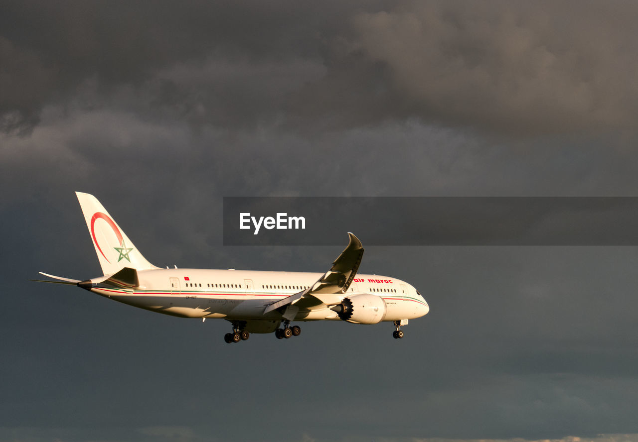 VIEW OF AIRPLANE FLYING IN CLOUDY SKY