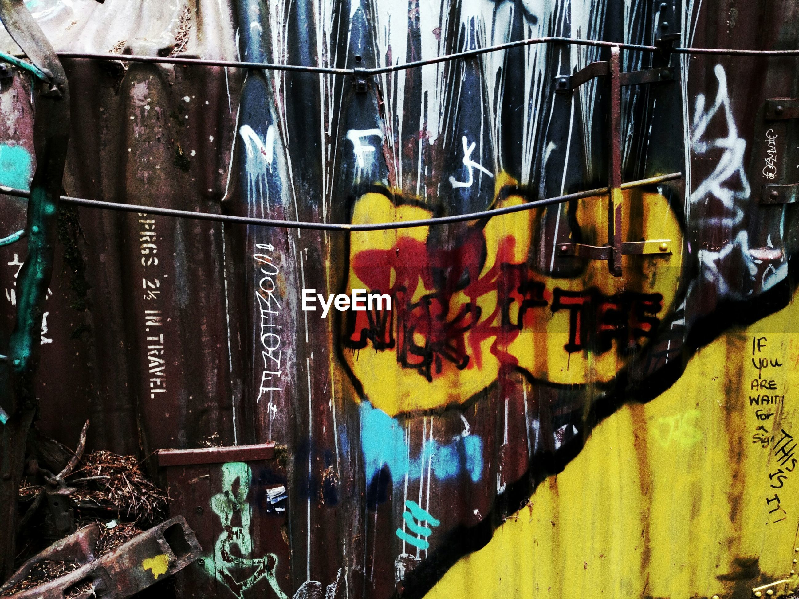text, graffiti, western script, communication, yellow, art, creativity, art and craft, non-western script, wall - building feature, multi colored, built structure, architecture, close-up, day, outdoors, no people, building exterior, street art, capital letter
