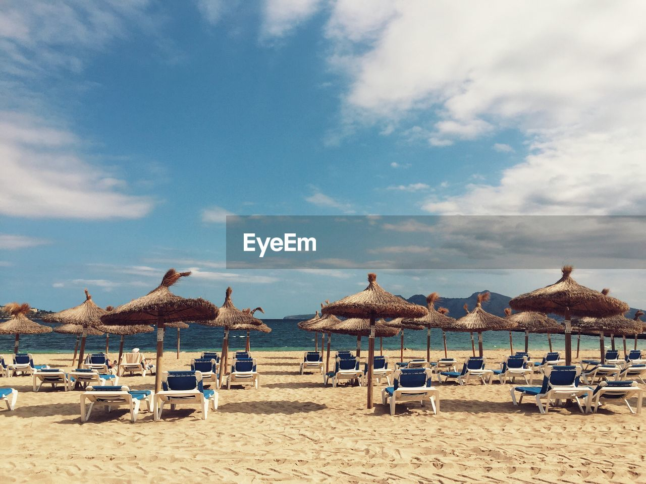Lounge Chairs By Thatched Roof Parasols At Beach Against Sky