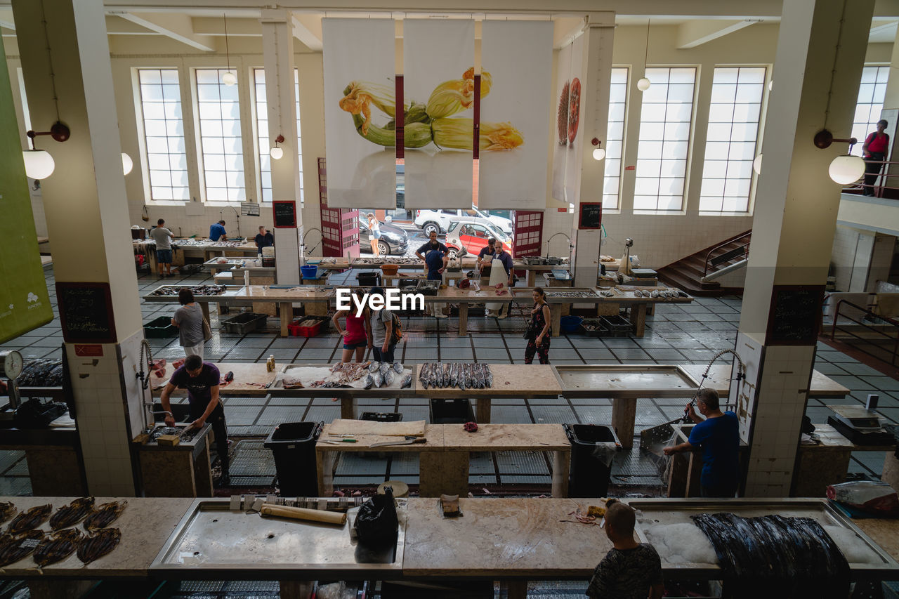 indoors, real people, group of people, lifestyles, crowd, day, men, large group of people, shopping, furniture, women, architecture, domestic room, window, adult, table, high angle view, incidental people