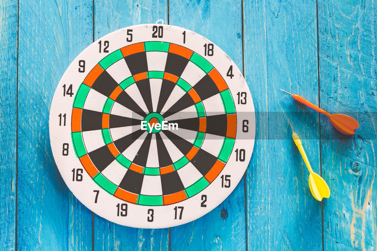 Close-Up Of Arrows And Dartboard On Table
