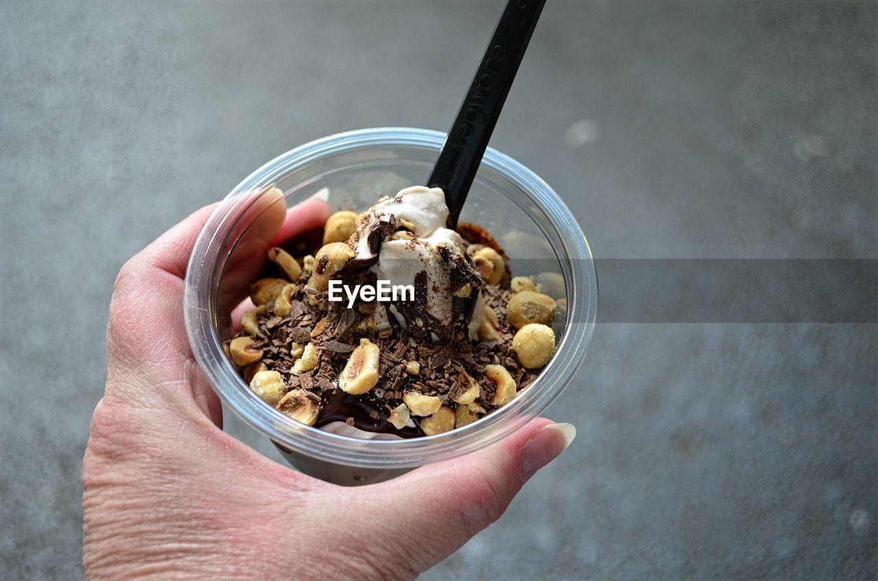 Close-Up Of Person Holding Ice Cream Sundae