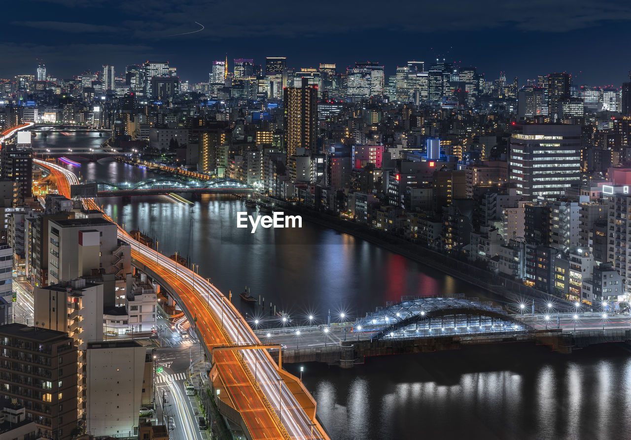 Aerial night view of the sumida river bridges and higways light-up with the skyscrapers of tokyo.