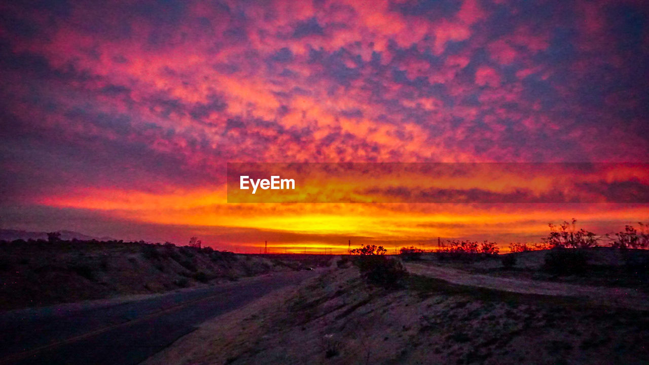 sunset, road, scenics, nature, orange color, beauty in nature, tranquil scene, landscape, tranquility, dramatic sky, no people, the way forward, sky, cloud - sky, sun, silhouette, transportation, outdoors, day