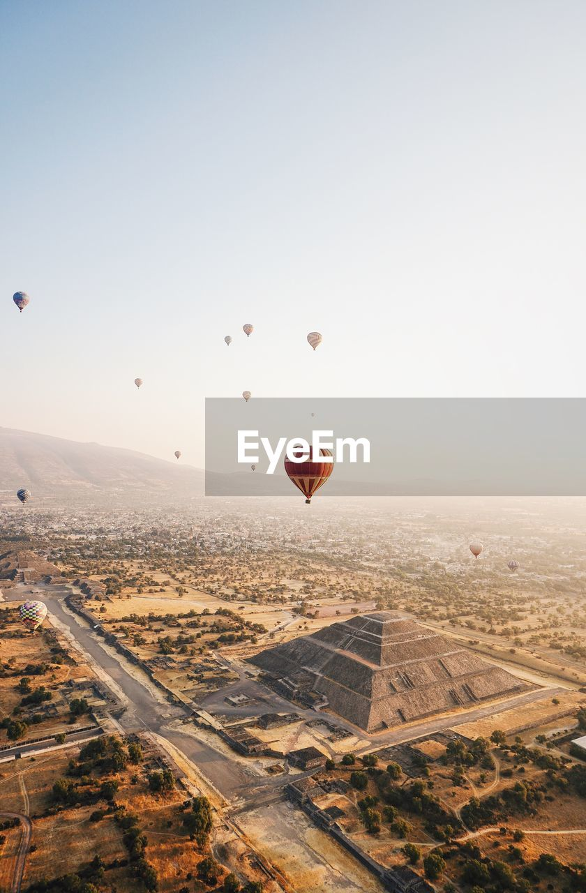 air vehicle, transportation, sky, balloon, hot air balloon, flying, mid-air, mode of transportation, nature, landscape, city, no people, environment, travel, architecture, scenics - nature, cityscape, beauty in nature, building exterior, airplane, outdoors, ballooning festival