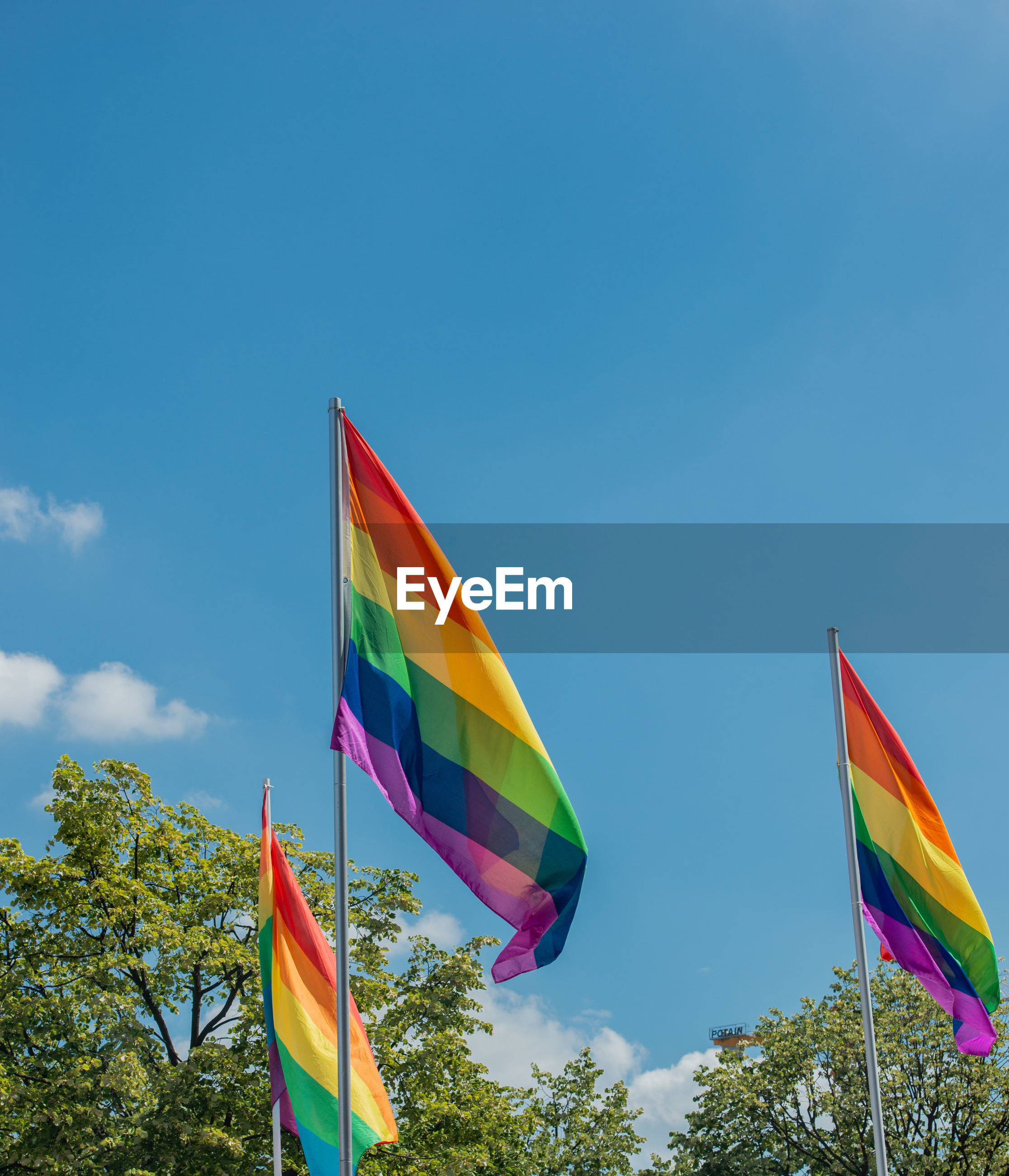 Low angle view of rainbow flags against sky