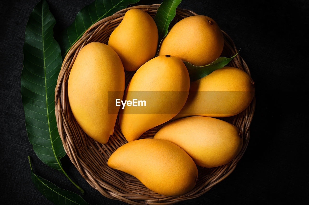 food, food and drink, wellbeing, healthy eating, freshness, basket, container, still life, indoors, fruit, high angle view, no people, close-up, group of objects, wicker, yellow, table, egg, black background, plant part