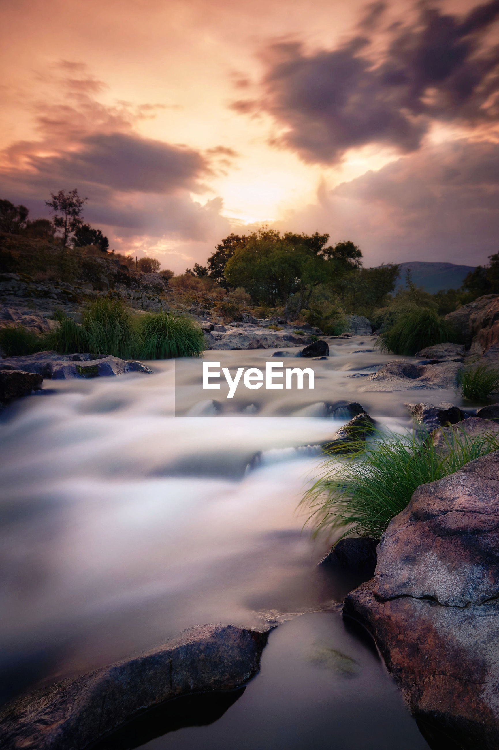 SCENIC VIEW OF WATER FLOWING THROUGH ROCKS DURING SUNSET