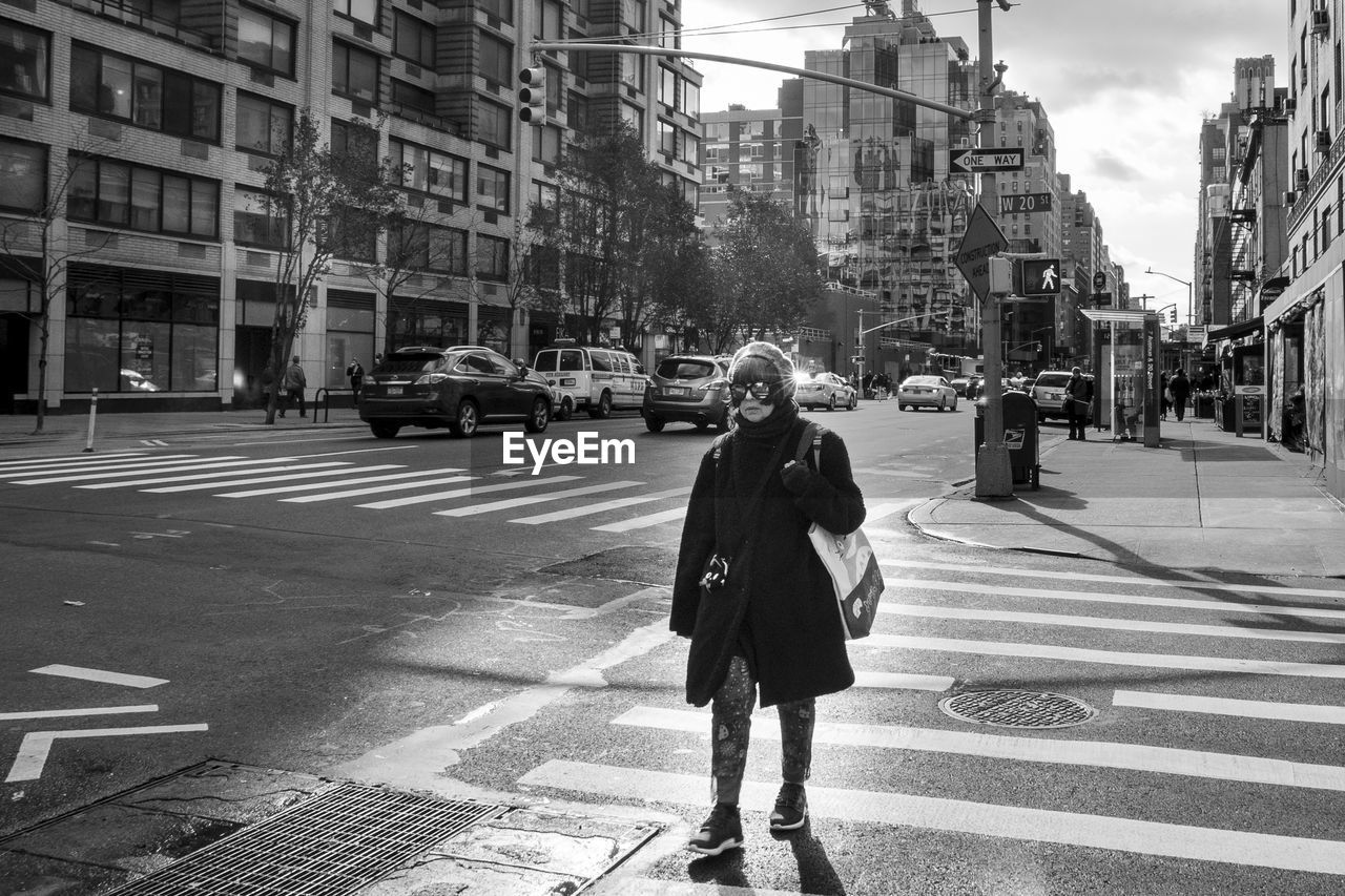 city, street, transportation, road, crossing, building exterior, architecture, crosswalk, road marking, zebra crossing, mode of transportation, one person, city life, real people, marking, full length, built structure, symbol, walking, motor vehicle, city street