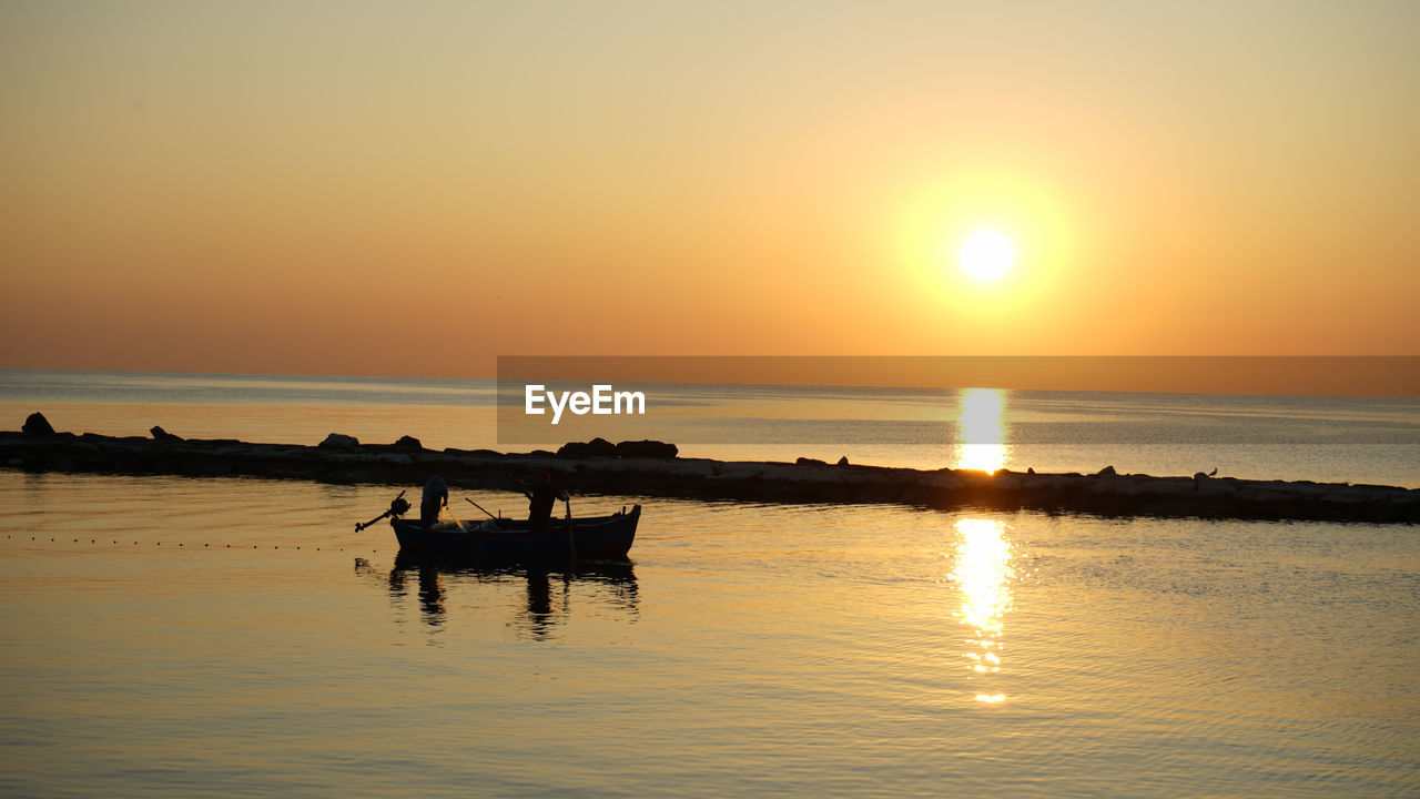 sky, sunset, water, sun, reflection, beauty in nature, silhouette, scenics - nature, orange color, waterfront, tranquility, nautical vessel, tranquil scene, sea, transportation, nature, idyllic, mode of transportation, sunlight, horizon over water, outdoors, bright, rowboat