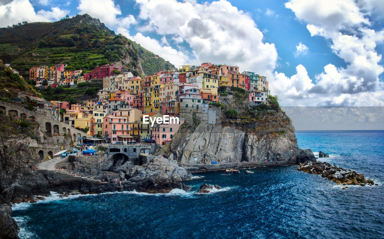 sea, rock - object, rock formation, water, sky, architecture, built structure, building exterior, beauty in nature, nature, cliff, cloud - sky, outdoors, mountain, day, no people, scenics, waterfront, horizon over water