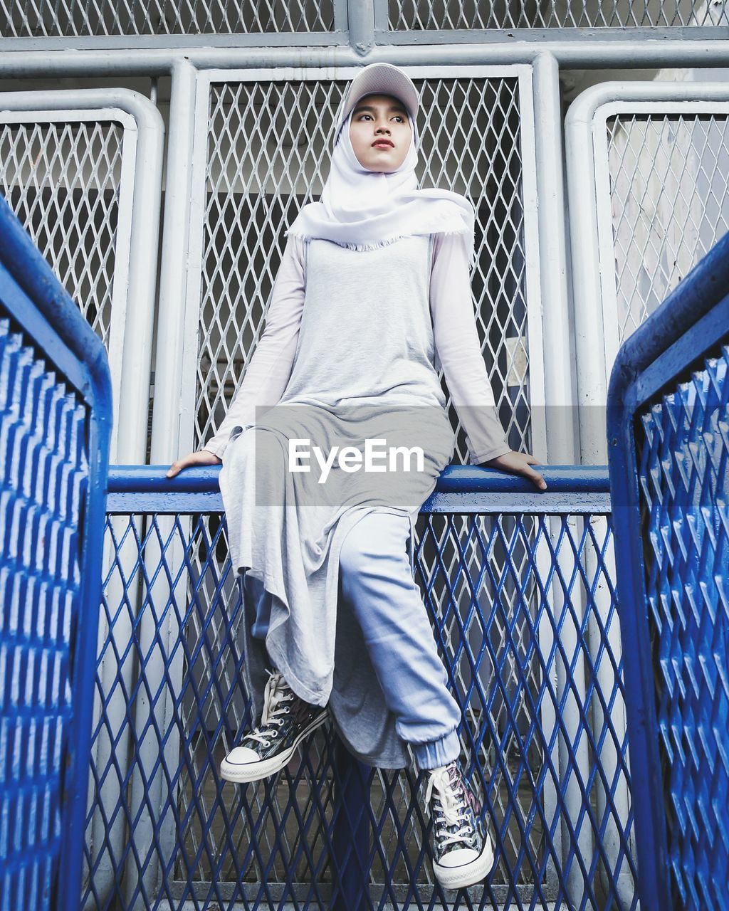 Low Angle View Of Woman Wearing Hijab Sitting On Railing