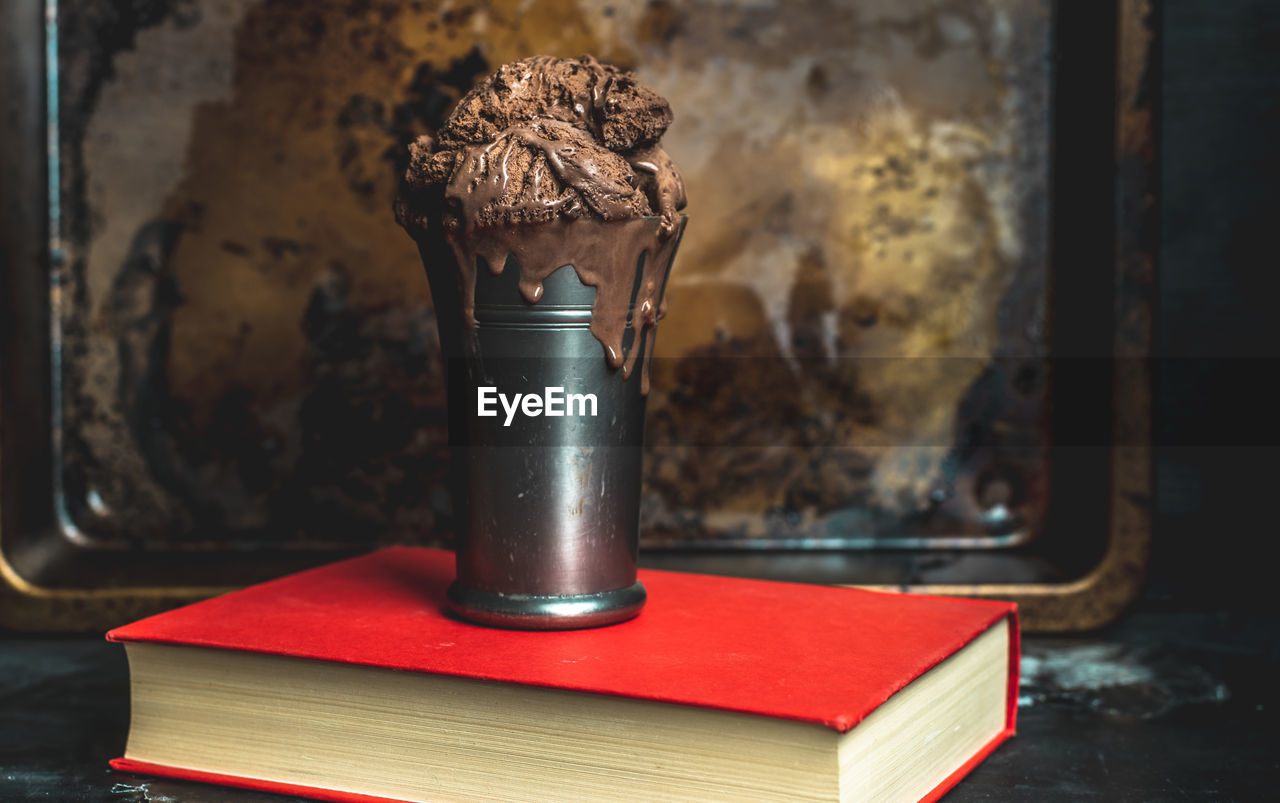 table, indoors, no people, still life, close-up, old, publication, metal, focus on foreground, book, container, weathered, day, freshness, red, nature, bad condition, food and drink, brown, wood - material