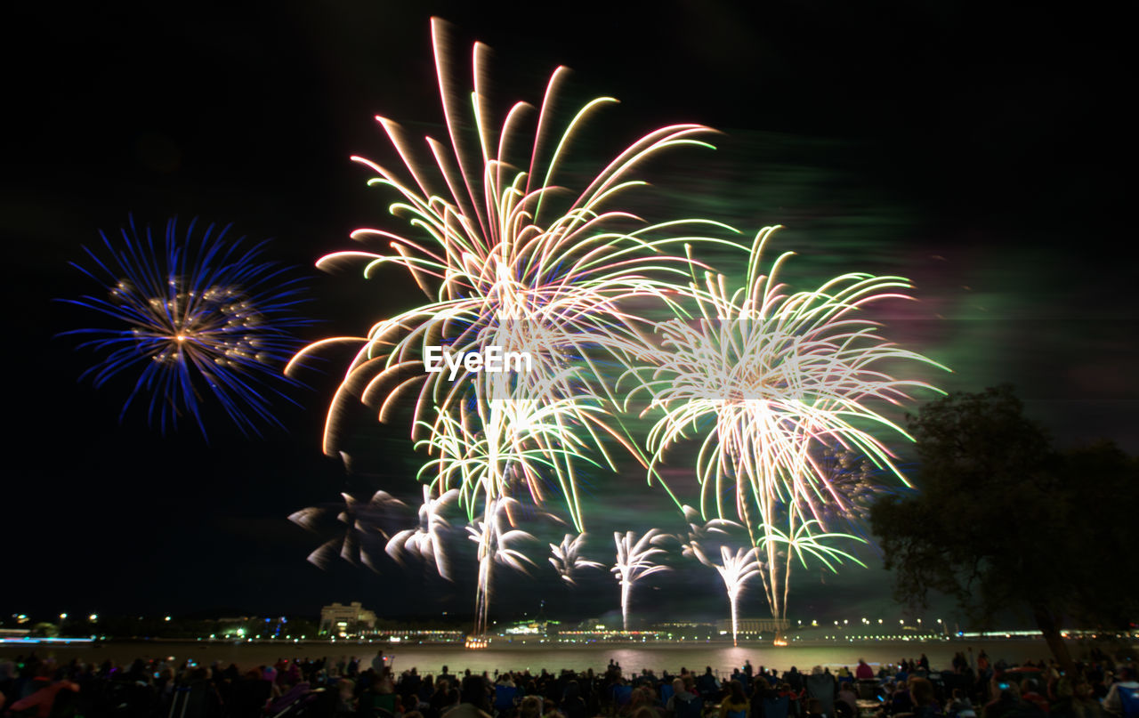 night, celebration, illuminated, firework, motion, event, arts culture and entertainment, firework display, glowing, group of people, long exposure, exploding, light, blurred motion, real people, sky, nature, firework - man made object, large group of people, crowd, outdoors, sparks, festival