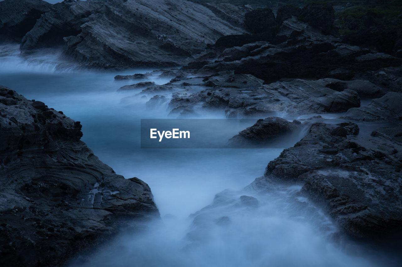 Long Exposure Of River Amidst Rocks