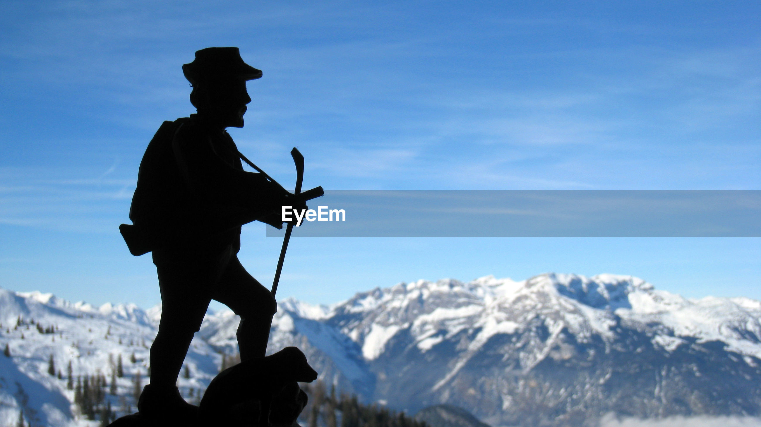 Silhouette figurine by snow covered mountains against sky