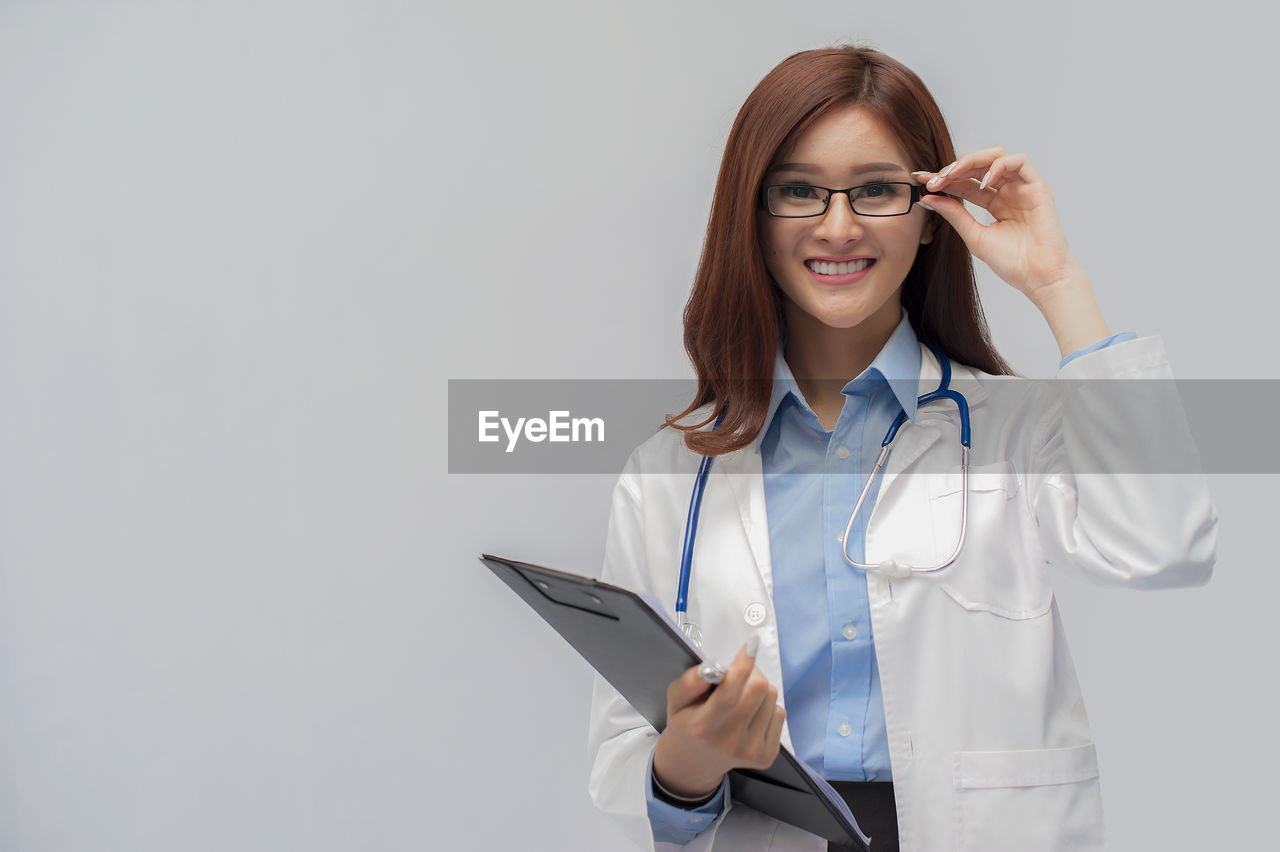 glasses, eyeglasses, holding, one person, front view, occupation, indoors, looking at camera, portrait, doctor, standing, copy space, women, professional occupation, technology, digital tablet, studio shot, adult, smiling, wireless technology, lab coat