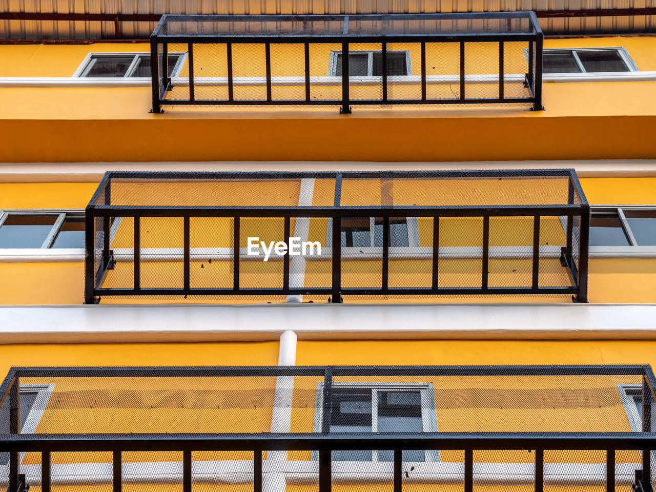 yellow, architecture, no people, building exterior, built structure, day, building, window, railing, outdoors, low angle view, seat, sunlight, transportation, orange color, full frame, side by side, absence, balcony, city