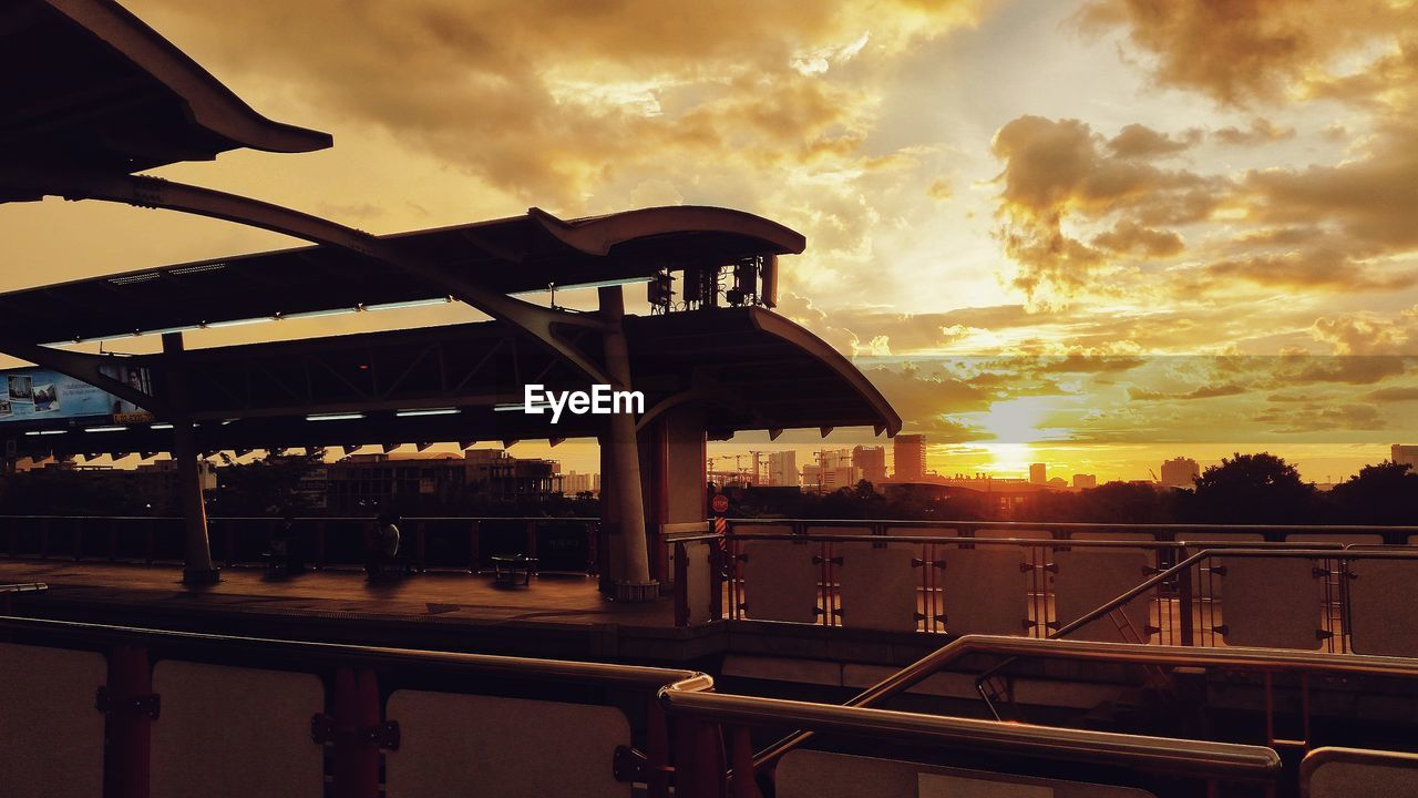 sunset, sky, railing, cloud - sky, built structure, sun, architecture, no people, silhouette, outdoors, building exterior, water, nature, city, day
