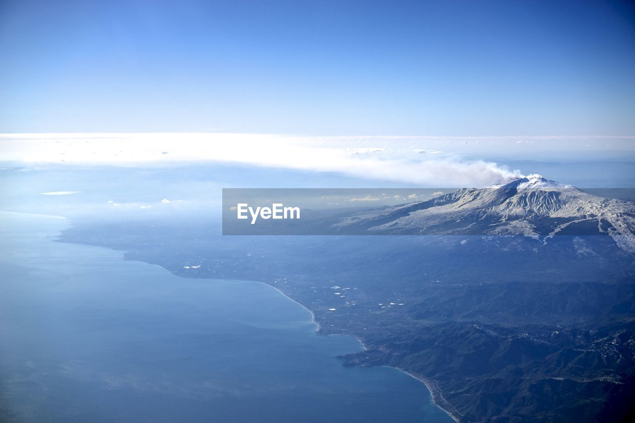Aerial View Of Snowcapped Mountains And Sea Against Blue Sky