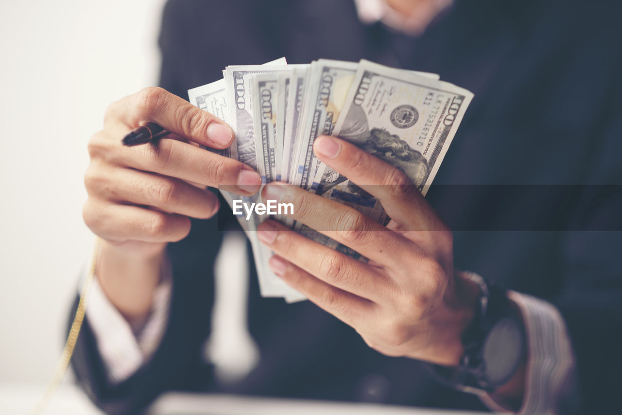 currency, finance, holding, wealth, midsection, human hand, paper currency, hand, business, real people, one person, human body part, indoors, front view, focus on foreground, close-up, men, lifestyles, adult, finger